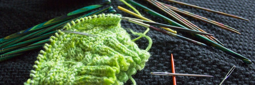 Knitting in progress with crochet and knitting equipment surrounding it